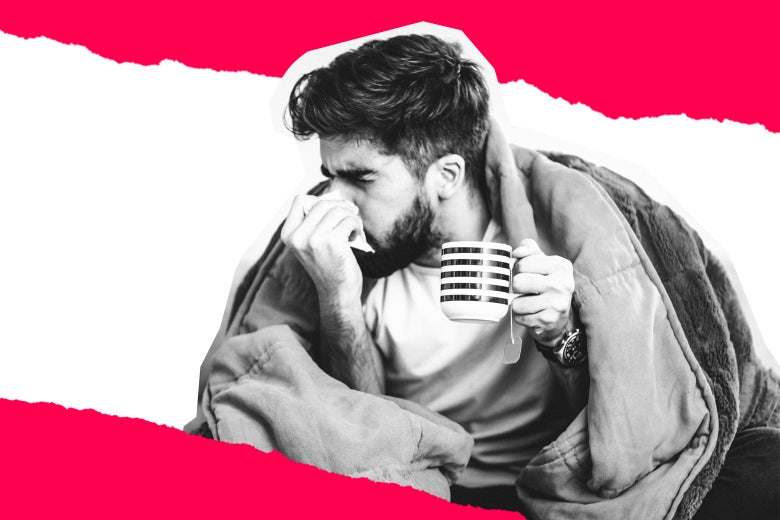 A sick man sniffling, with a blanket and a mug of tea