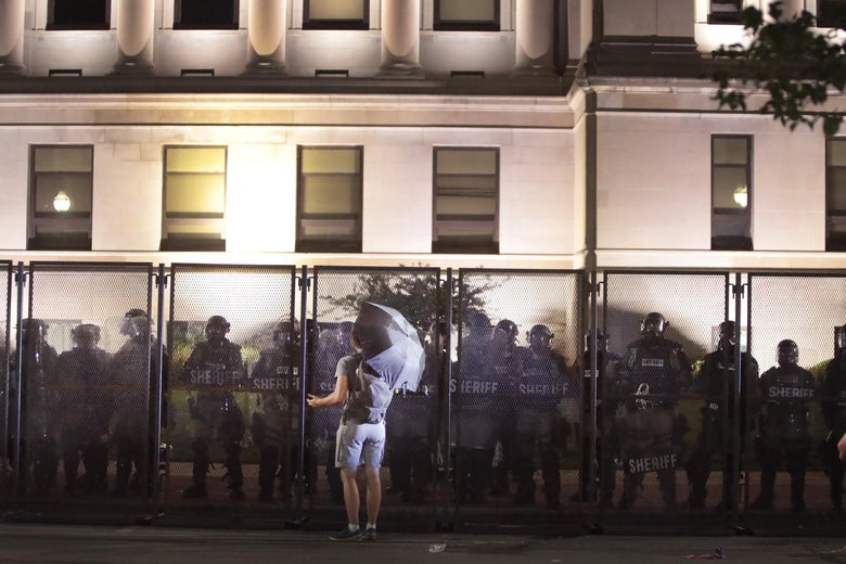 Police guard the Kenosha County Courthouse during a third night of unrest.
