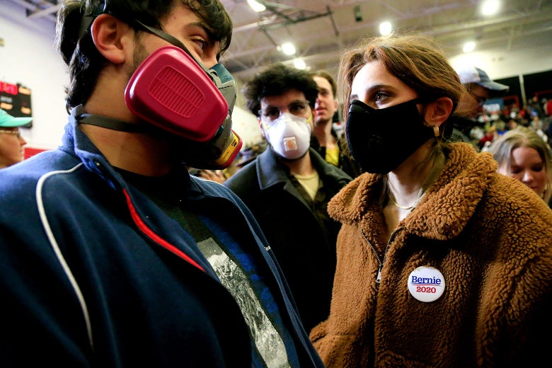 Three people wearing masks while standing in a crowd inside.