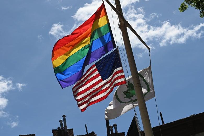 A rainbow flag and an American flag flying on a flagpole.