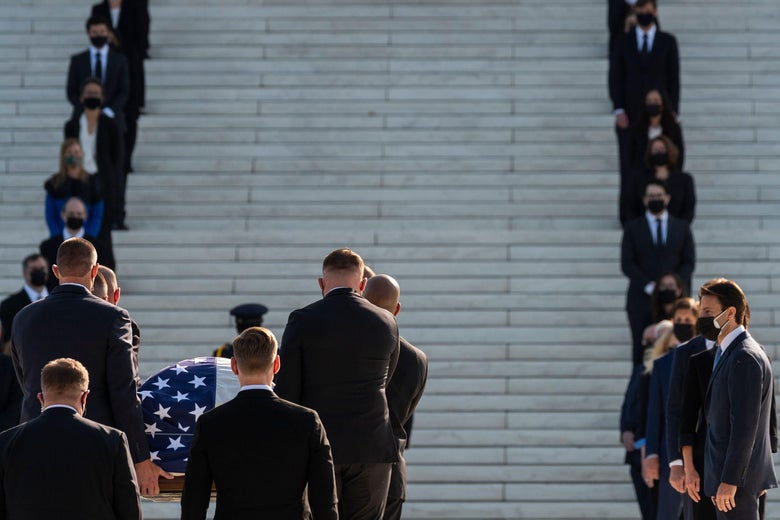 People in suits stand on the steps of the Supreme Court as a casket with an American flag is carried up the steps.