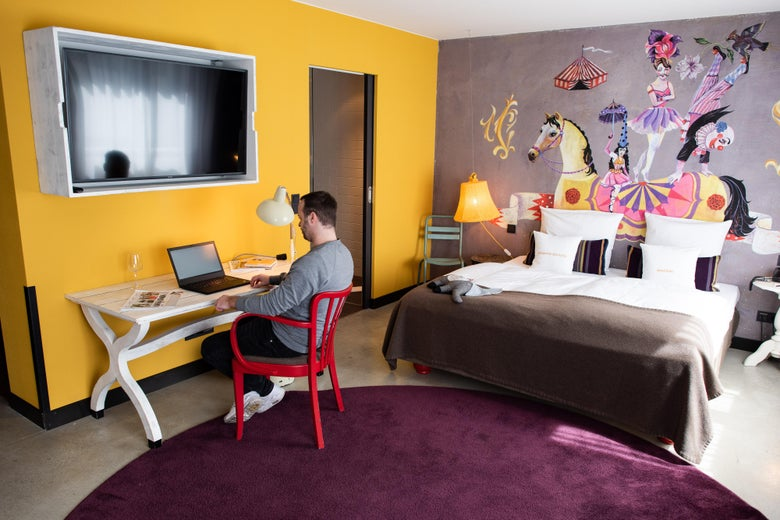 A man sits at a desk, typing at a laptop, underneath a TV screen. Behind him, a huge bed sits against a well decorated wall.