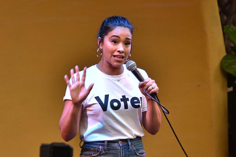 "Gina Rodriguez speaking at a rally, wearing a shirt that says ""Vote."""