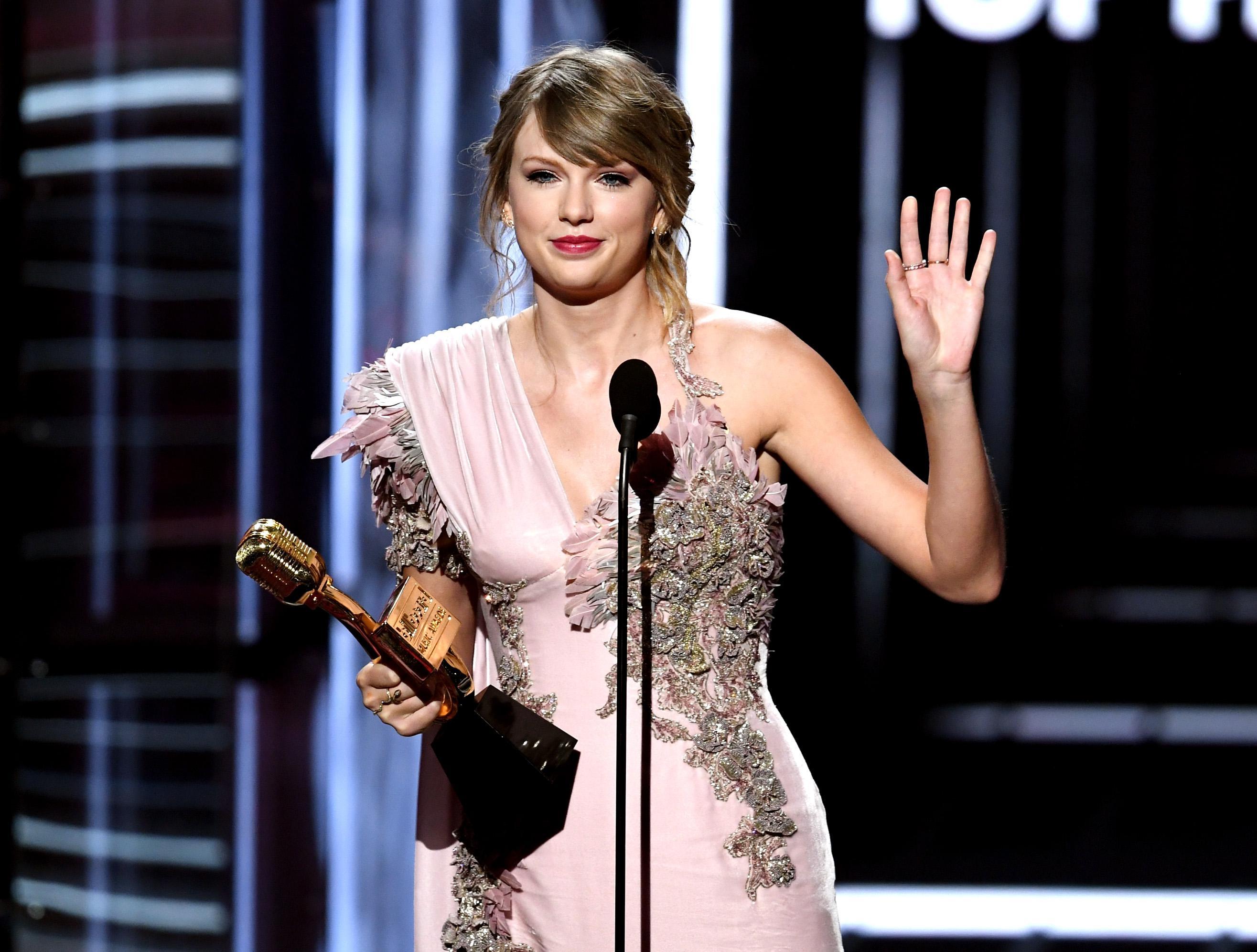 Taylor Swift waving goodbye at an awards show.