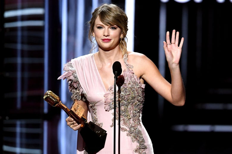 Taylor Swift waving goodbye at an awards show.