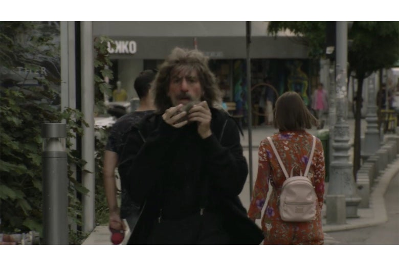 A still from Borat showing Borat walking toward camera on a city street, in front of a Yokko shop.