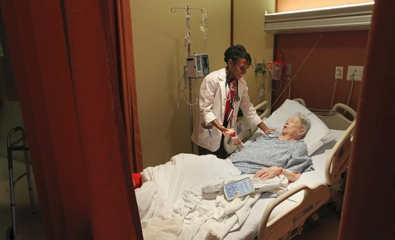 Boston University Medical student Erica Perry, left, checks on patient Alma Conroy at the Boston Medical Center.