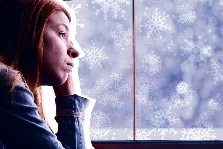 A forlorn-looking woman stares out the window at snow.