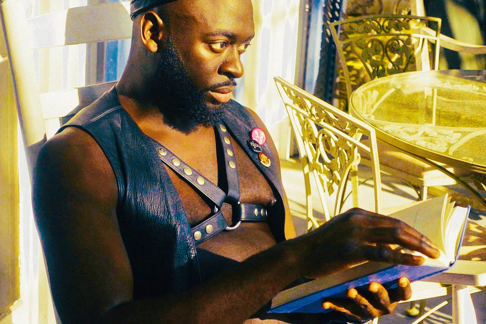 A man sitting outdoors wearing a leather vest and harness reading a book