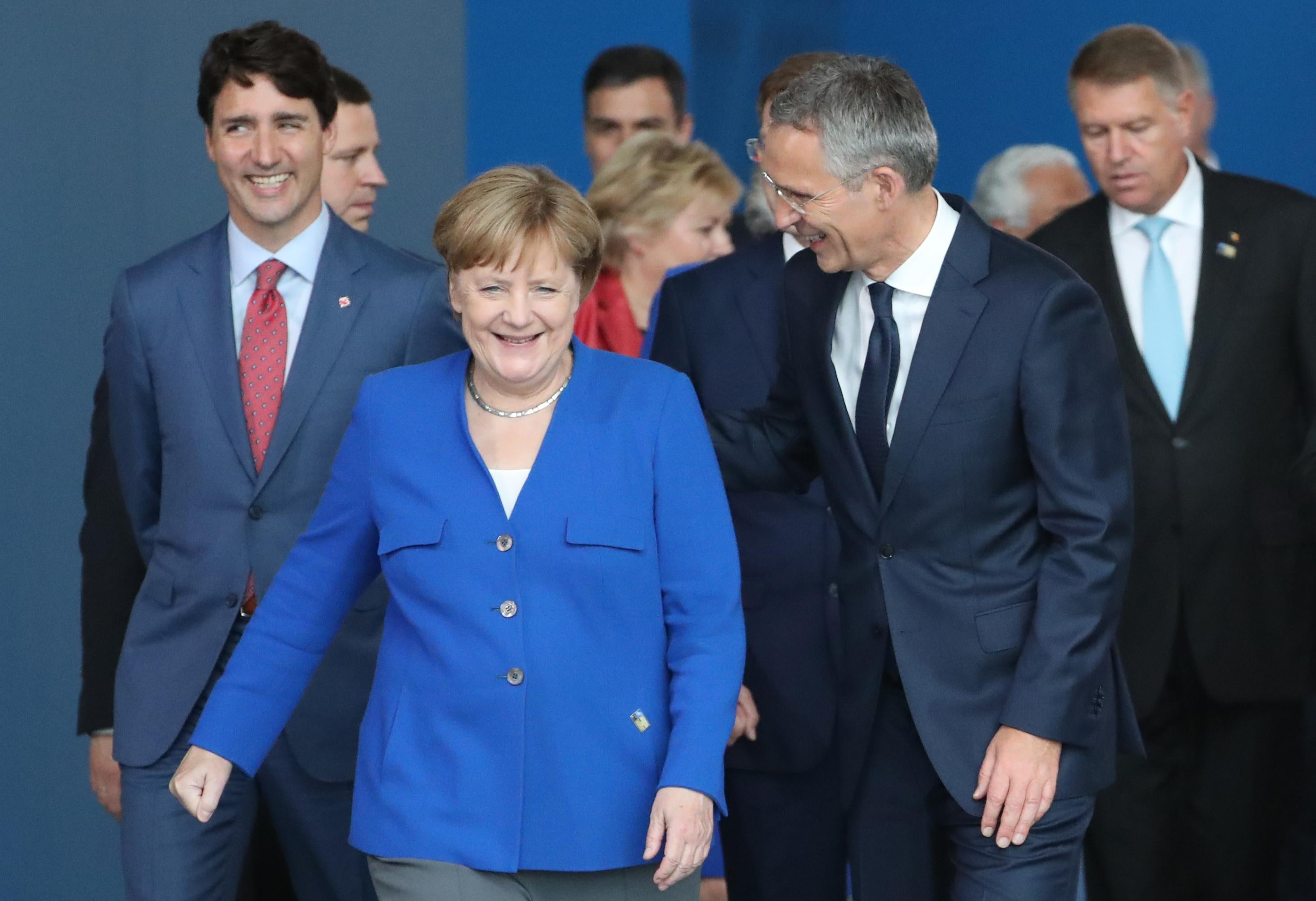 Angela Merkel and other world leaders walk toward the camera.