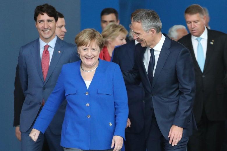 Angela Merkel and other world leaders walk toward the camera.