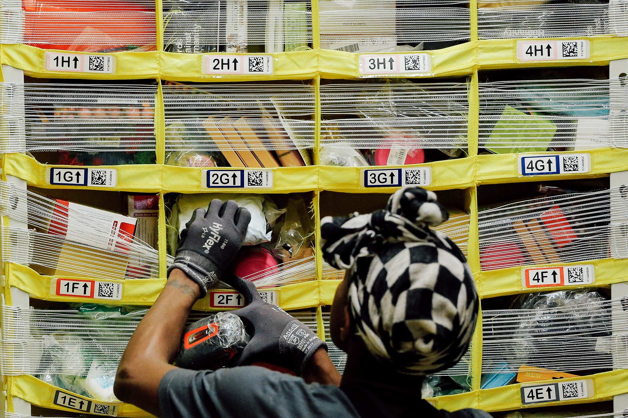 A worker sorts products into bins inside an Amazon Fulfillment Center.