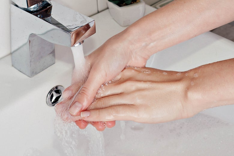 Hands are seeing being washed under a running faucet.