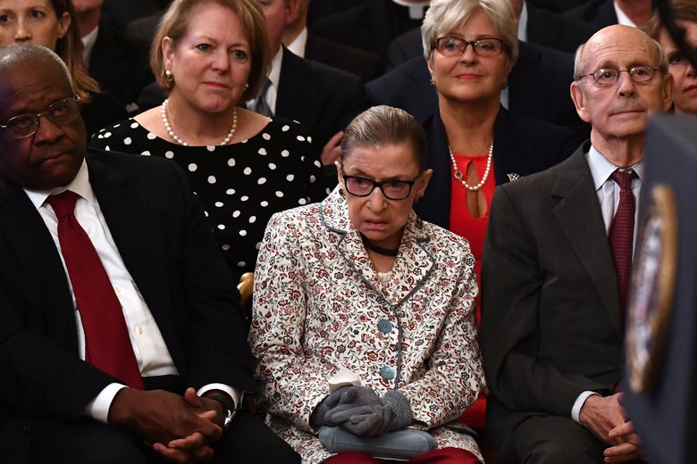 Ginsburg, seated, looks to her right.