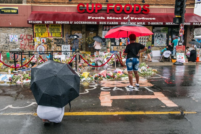 People with umbrellas look at memorial for George Floyd in front of a Cup Foods store Minneapolis.