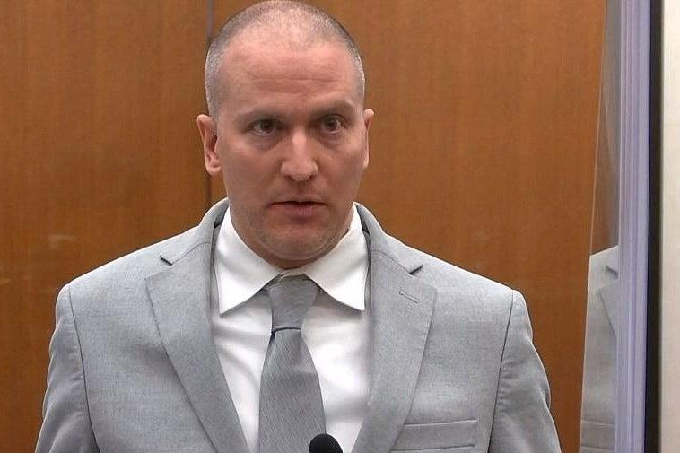 Derek Chauvin stands in a gray suit.