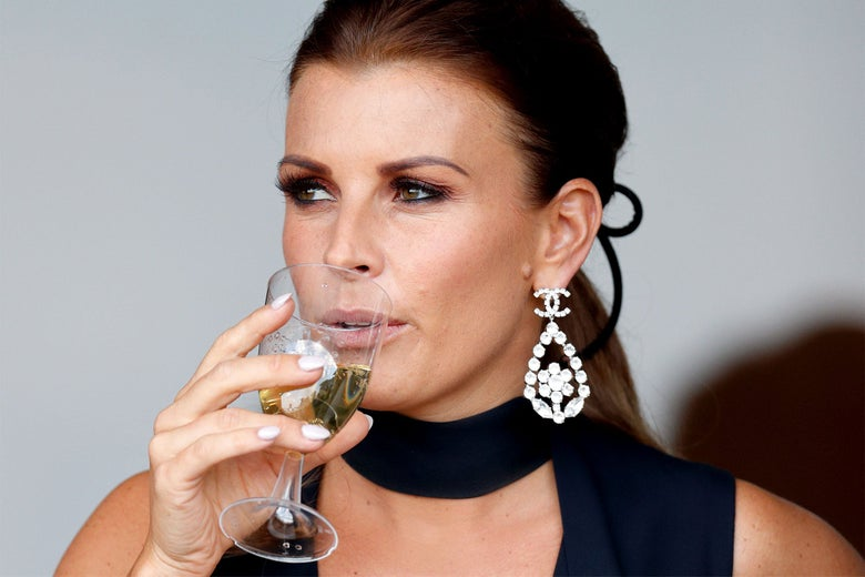 Coleen Rooney sipping from a glass with smoldering intensity in her eyes.