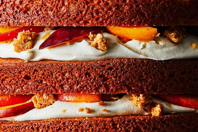 Three layers of cake filled with white cream, peaches, and crumbs.