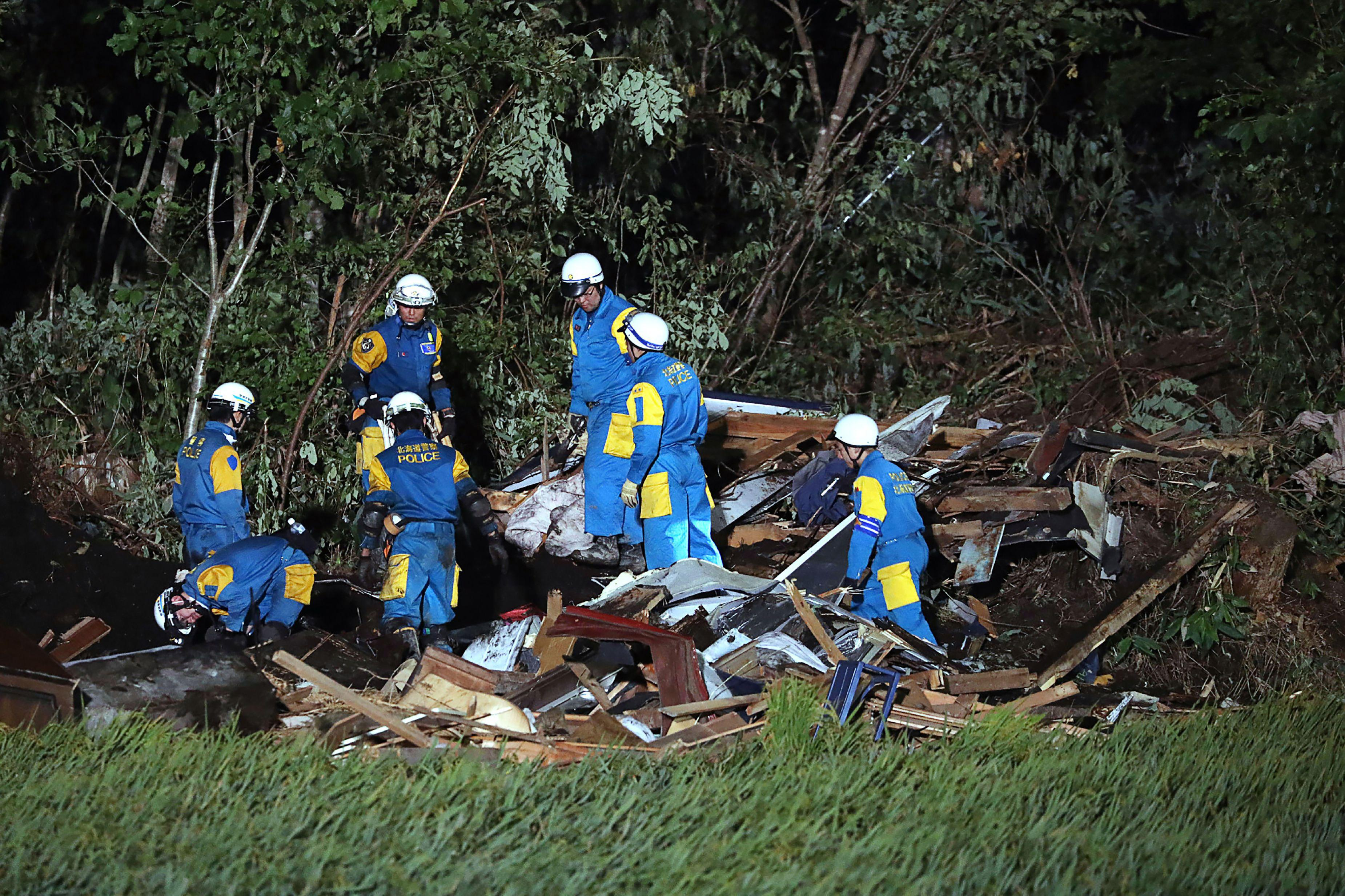 Japanese policemen work during a rescue operation in the area affected by landslides triggered by the earthquake.