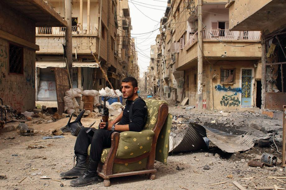 A member of the Free Syrian Army holds his weapon as he sits on a sofa in the middle of a street in Deir al-Zor on April 2, 2013.