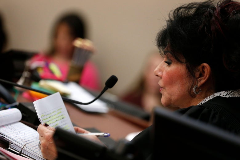 Judge Rosemarie Aquilina reads a statement from Larry Nassar during the sentencing phase in Ingham County Circuit Court on Wednesday in Lansing, Michigan.