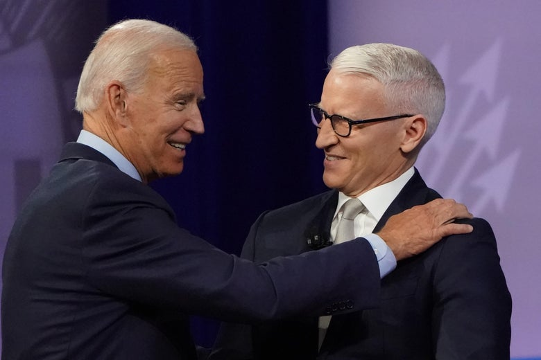 Joe Biden places his right hand on Anderson Cooper's right shoulder as both men smile.
