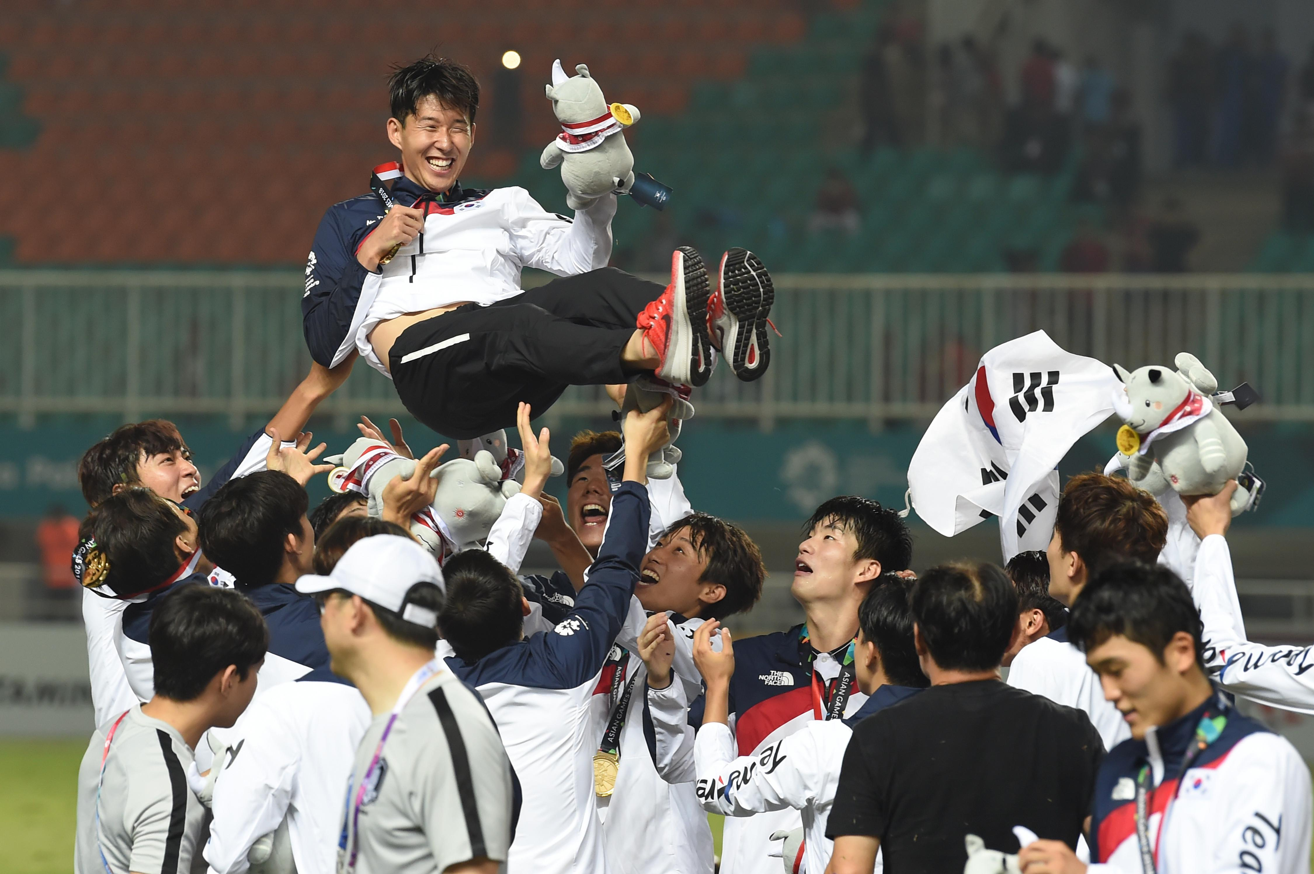 South Korea's players toss their teammate Son Heung-min in the air after the victory ceremony for the mens football competition at the 2018 Asian Games in Bogor on September 1, 2018. (Photo by Arief Bagus / AFP)        (Photo credit should read ARIEF BAGUS/AFP/Getty Images)