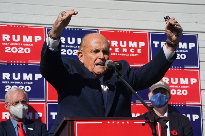 Giuliani stands at a podium in front of Trump 2020 signs and raises his hands, as two men stand in the background.