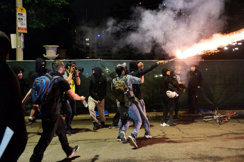 Protesters tackle a man setting off fireworks.