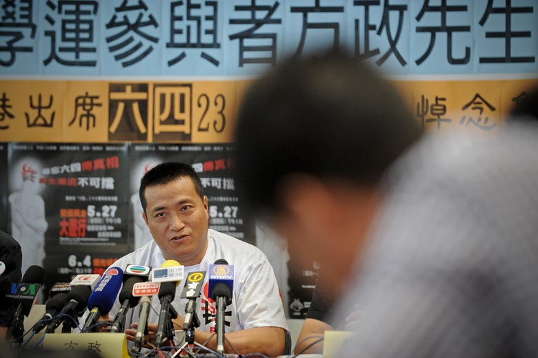 Tiananmen amputee Fang Zheng (L) addresses a press conference in Hong Kong on June 1, 2012 ahead of the June 4th candlelight vigil to be held in the city to mark the crackdown on the pro-democracy movement in Beijing's Tiananmen Square in 1989.  Twenty years ago, a Chinese tank pummeled into then student athlete Fang Zheng as he fled Tiananmen Square. He lost his legs and his livelihood as he was reduced to selling cigarettes at a street stall.   AFP PHOTO / Philippe Lopez        (Photo credit should read PHILIPPE LOPEZ/AFP/GettyImages)
