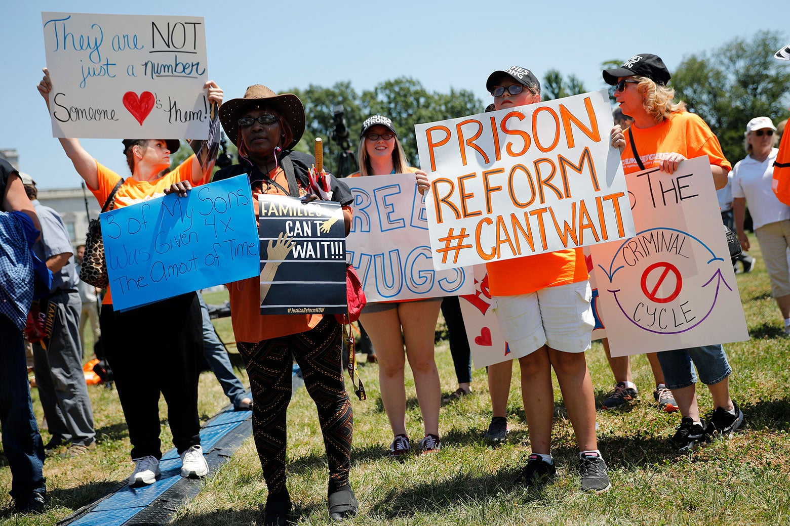 Protesters hold signs during a rally calling for criminal justice reform.