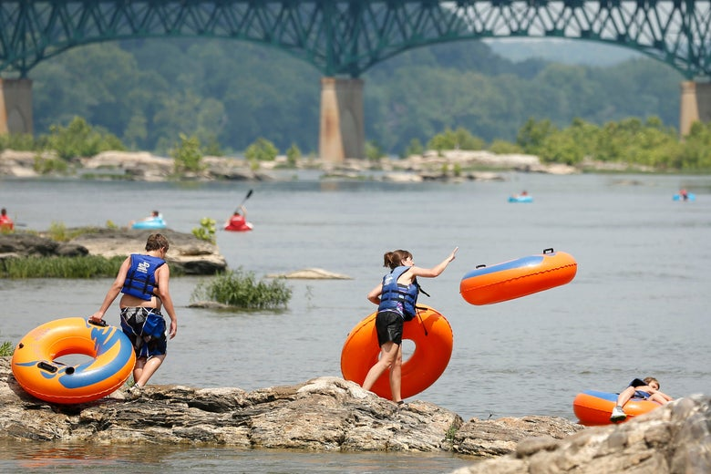 A woman hurls an inner tube into the Potomac River in Harpers Ferry, Virginia.