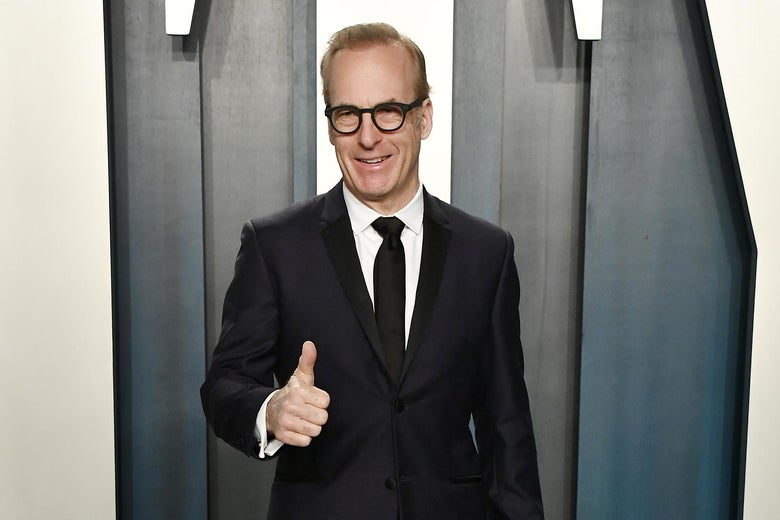 Bob Odenkirk in a black suit, standing in front of a Vanity Fair sign at their party, giving a thumbs up.