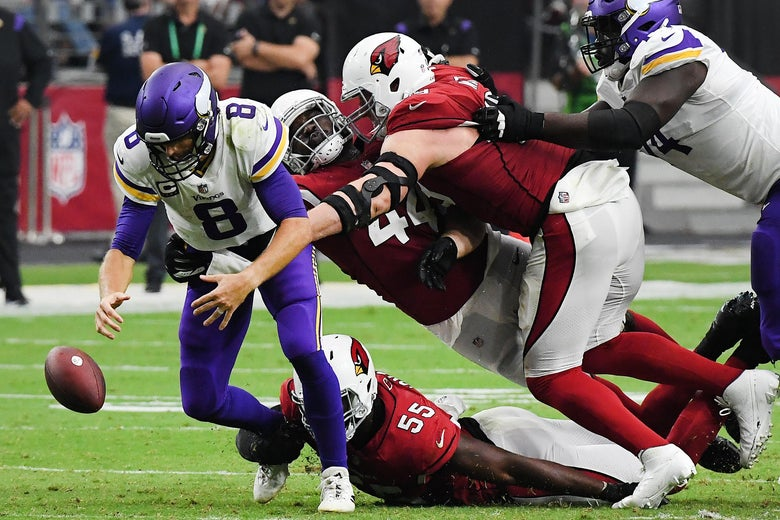 Cousins staring at the football on the ground that's been knocked out of his hands as three giant Cardinals envelop him.