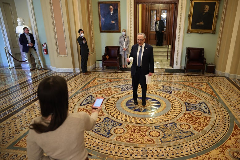 Schumer stands in the center of a room speaking to a reporter several feet away, recording the interview on a phone