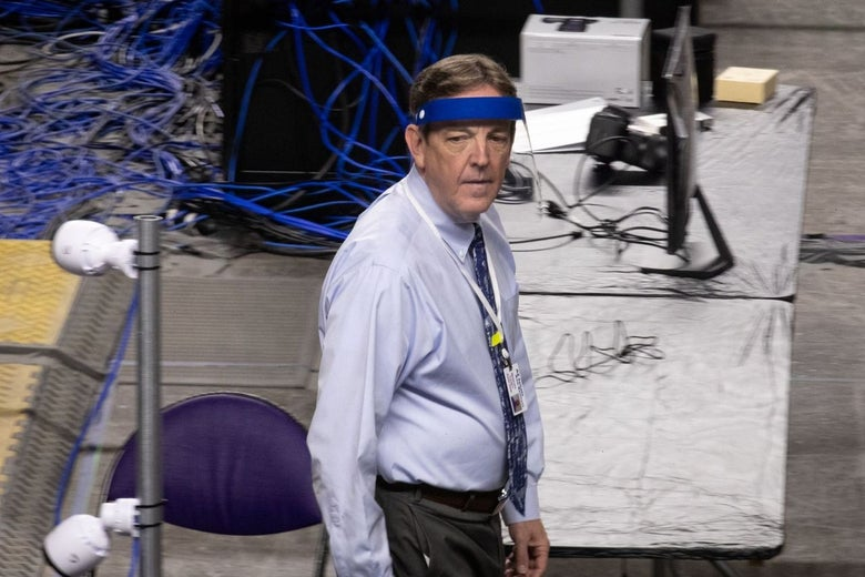 Bennett stands on the audit floor wearing a visor and looking serious.