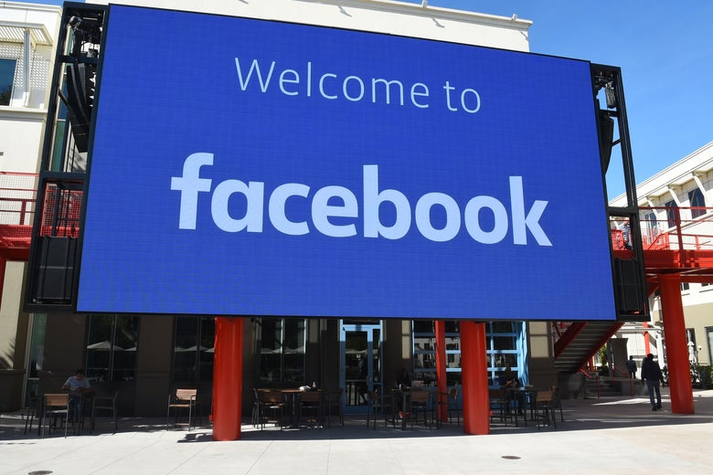 """A large blue sign reads """"Welcome to Facebook."""""""