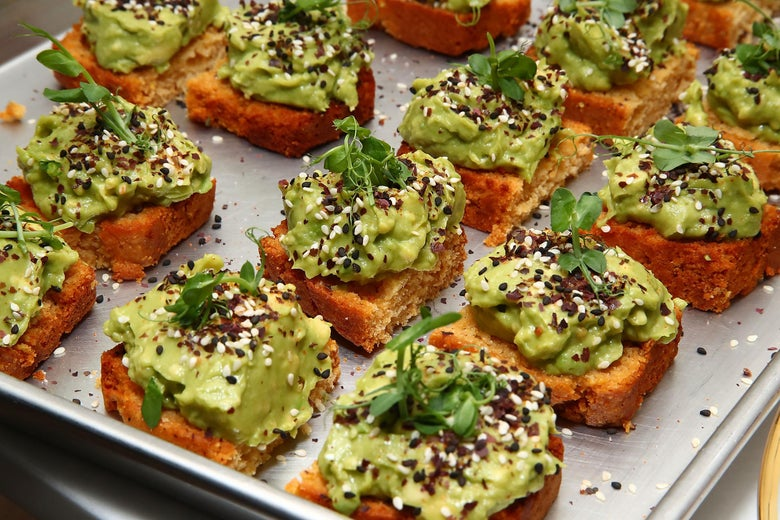 Rows of avocado toast sprinkled with sesame seeds sit on a metal sheet.