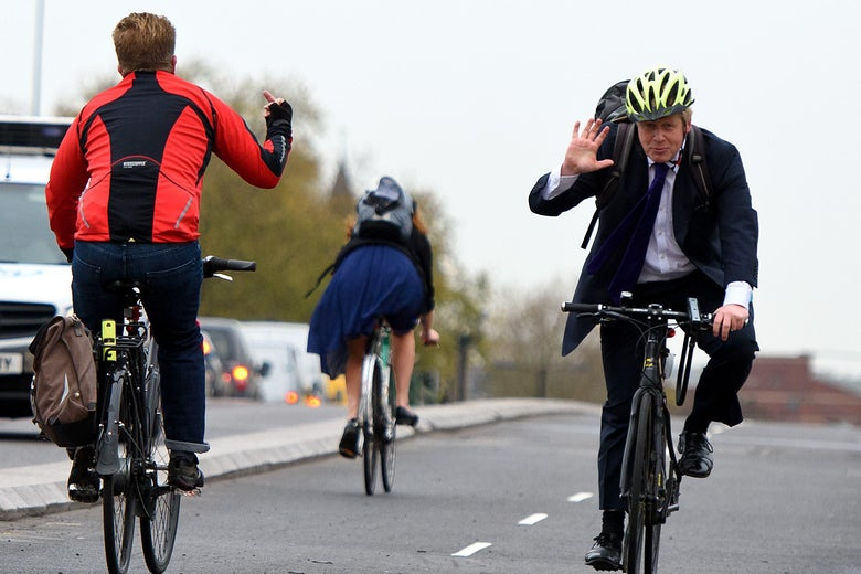 A biker (L) flips off Boris Johnson (R) as he waves and approaches on a bike.