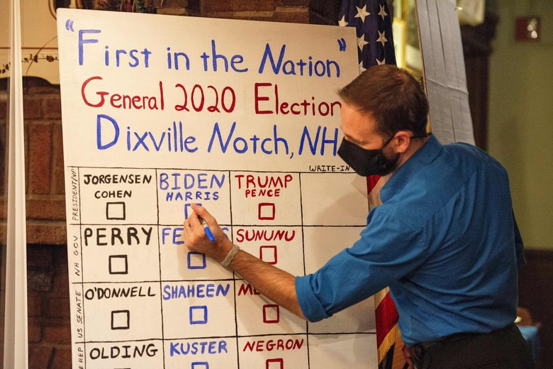 An election worker writes the Dixville Notch vote tally in colored pen on a dry erase board.