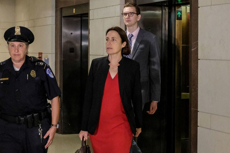 Hill, wearing a red desk and jacket, walks out of an elevator behind a police officer.