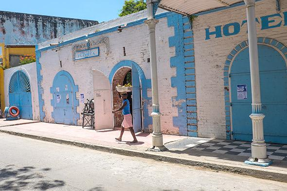 A woman carries a basket of bananas on her head outside the Hotel Florita in Jacmel, May 5, 2014.