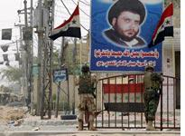 Iraqi soldiers stand under a poster of Moqtada al-Sadr. Click image to expand.