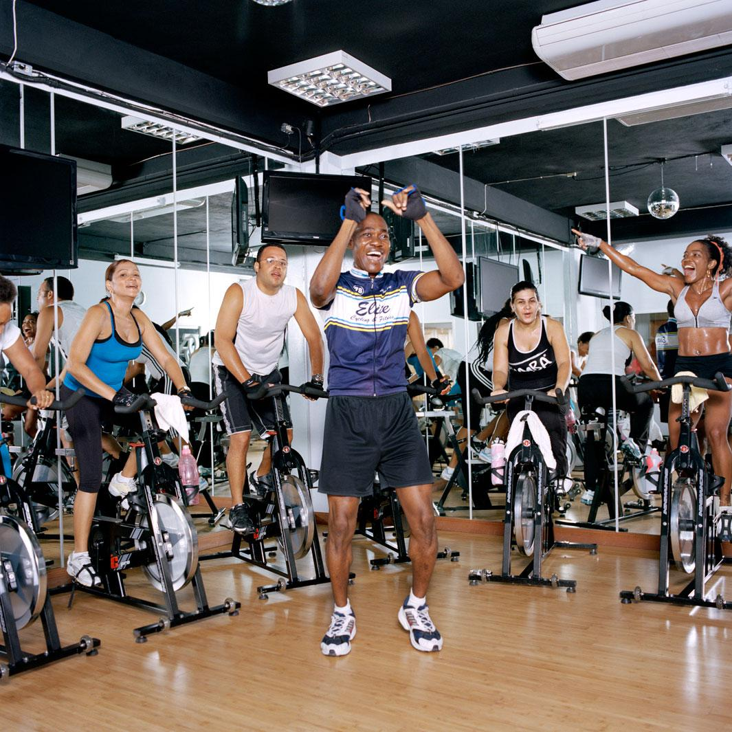 A six a.m. spinning class at Ultimate Fitness. In a white T-shirt, the vice president of Access Haiti, one of the country?s major Internet providers. With her hands in the air, Claudie Marsan, a prominent corporate lawyer.  Pétion-ville. Haiti