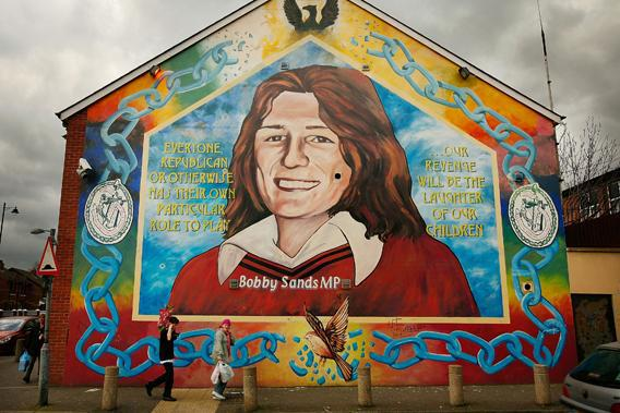 A couple walk past a mural depicting Bobby Sands, who died following a hunger strike in prison, in Belfast, Northern Ireland.