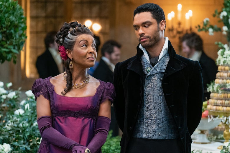 Adjoa Andoh and Regé-Jean Page exchange a look in a ballroom, a tower of macarons behind them.