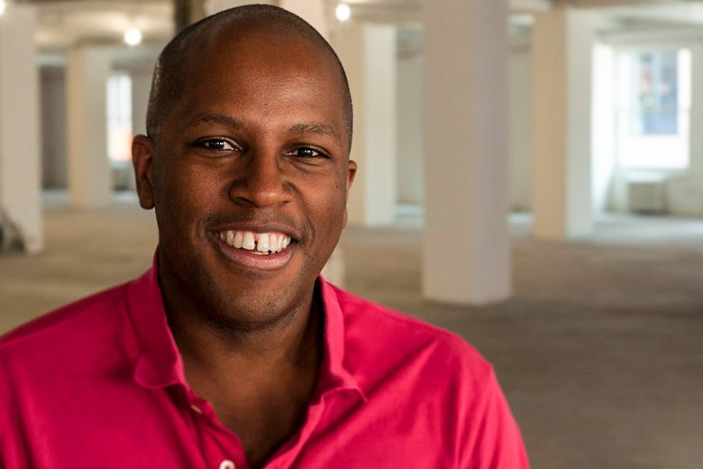 A smiling young black man wearing a bright pink shirt.