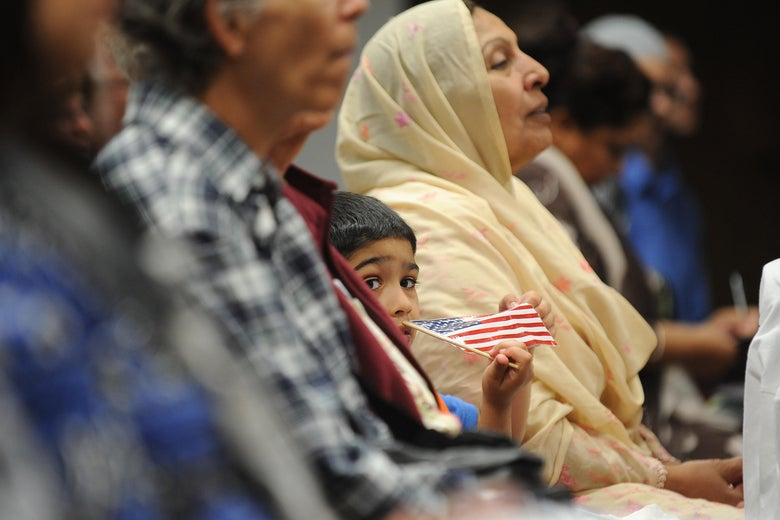 A boy sitting in the audience holds a small American flag next to an older woman wearing a headscarf