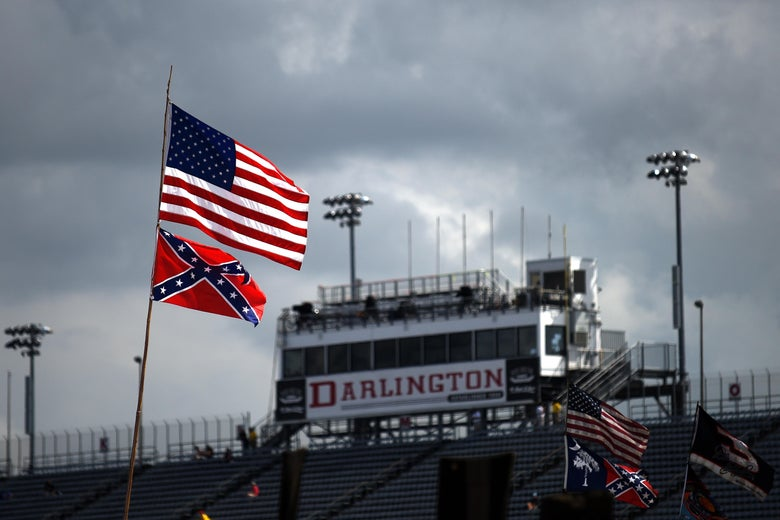 American and Confederate flags are seen flying over a stadium that features a large Darlington sign.