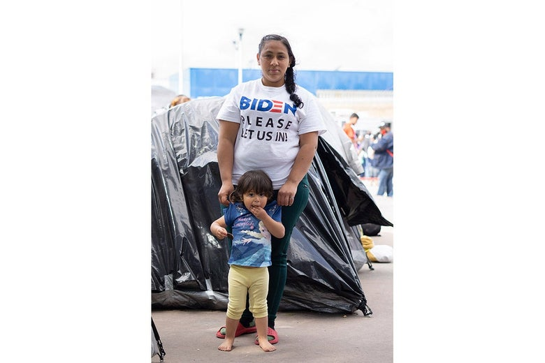 """A woman in a T-shirt that says, """"Biden, please let us in,"""" stands behind a small child."""